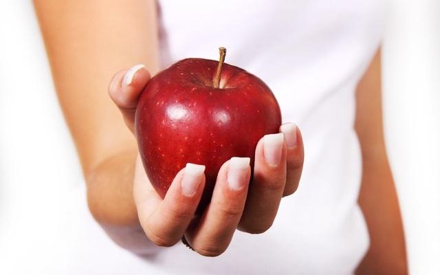 Kobieta trzymająca w dłoni jabłko