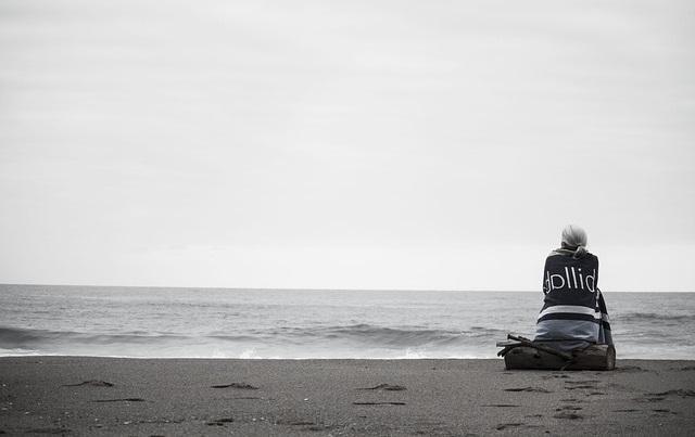 Kobieta siedząca na brzegu morza
