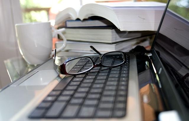 Kompuetr na którym leżą okulary a obok jest stos książek