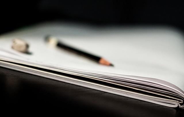Notatnik na którym leży ołówek i kulka papieru