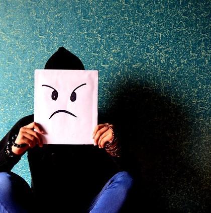 człowiek zasłania twarz kartką z narysowaną gniewną miną