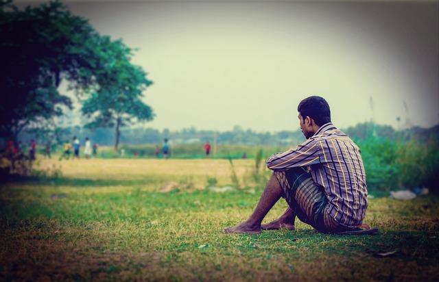 Człowiek siedzący na trawie