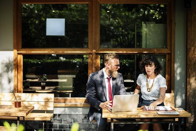 Dwoje ludzi rozmawia przy laptopie