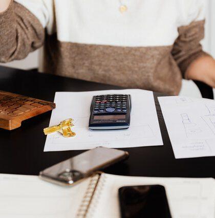 Kobieta przy komputerze z kalkulatorem